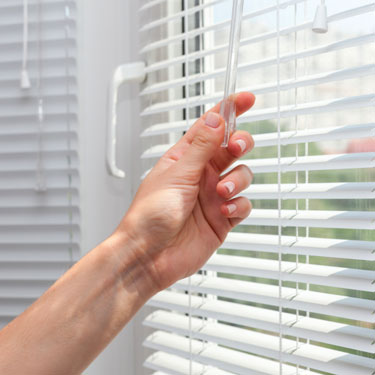 hand closing the blinds