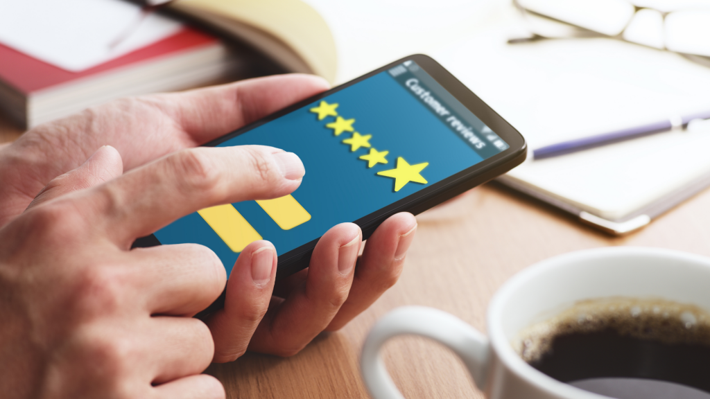 hands filling out 5 star review on mobile device