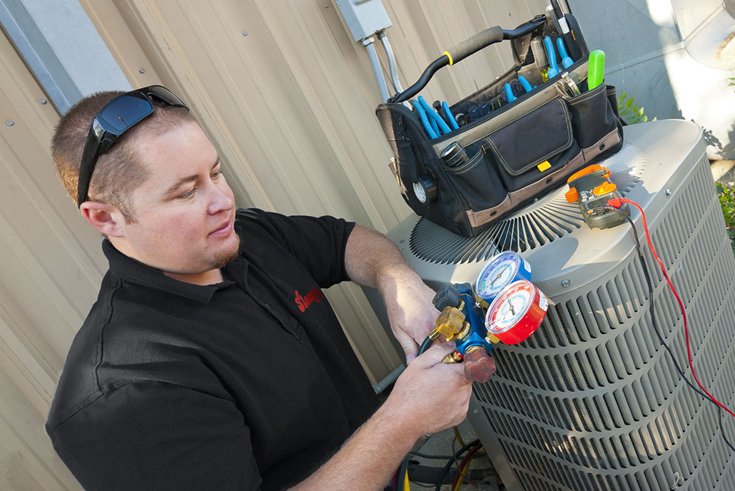 Slomins technician repairing ac condenser