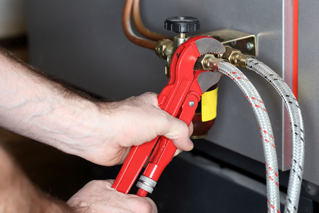 Heating technician tightening oil valve