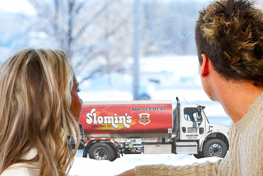 slomins oil truck delivering to couple looking out of a window.