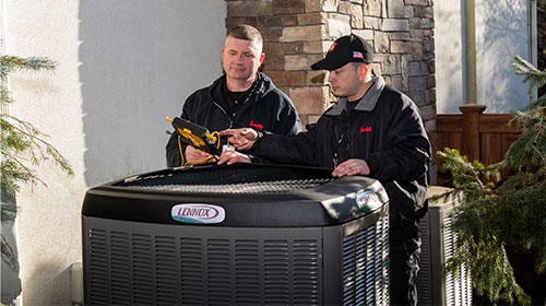 slomins cooling technicians inspecting an AC unit