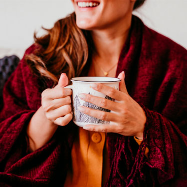woman with tea and a blanket