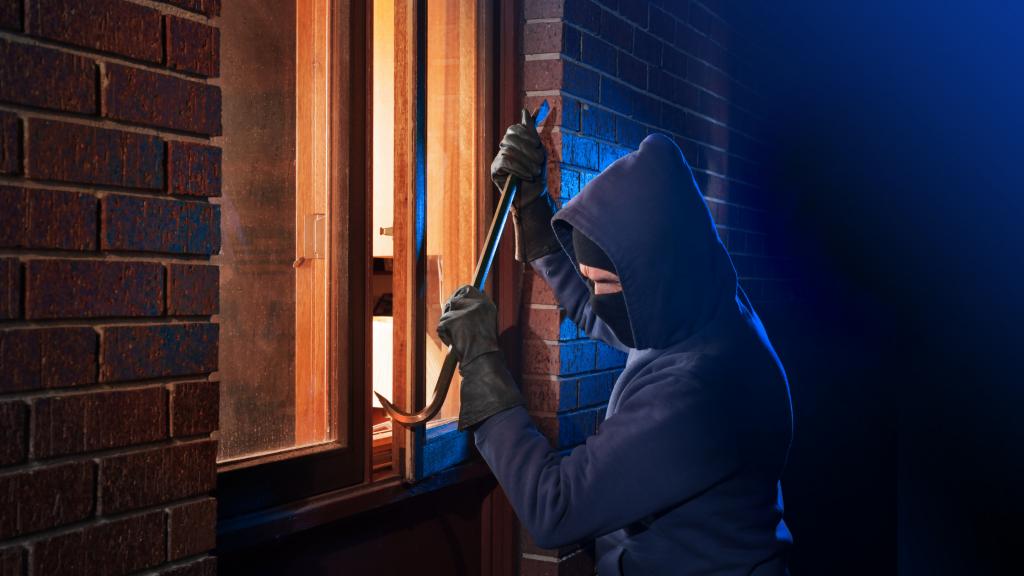 burglar prying open window with crowbar