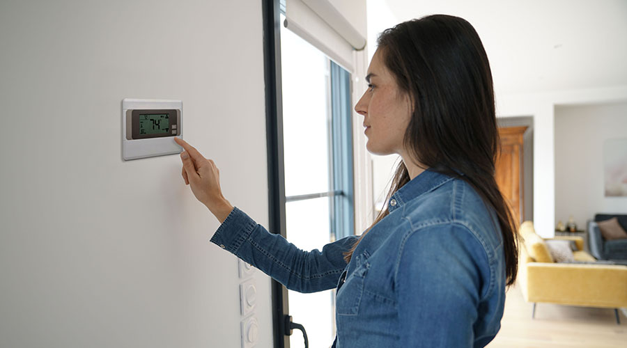 Woman turning on slomins HVAC unit to filter air